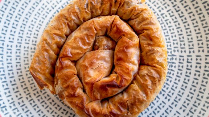Burek rullad till snäcka på fat. Burek är en typ av filopaj.